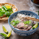 Close view of pho bo in traditional bowl, garnished with basil, mint, lime, on concrete background - PhotoDune Item for Sale