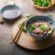 Traditional vietnamese noodle soup pho in bowl, garnished with basil, mint, lime, on concrete - PhotoDune Item for Sale