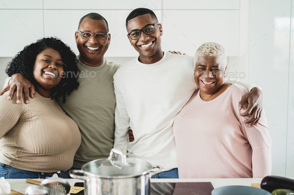 Happy black family cooking inside kitchen at home - Main focus on father face - Stock Photo - Images