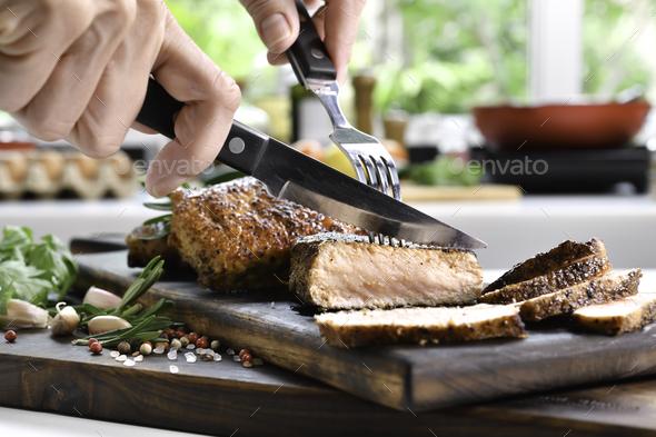 Slicing grilled pork steaks - Stock Photo - Images