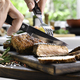 Slicing grilled pork steaks - PhotoDune Item for Sale