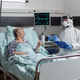 Doctor dressed in ppe suit with face shiled discussing with senior patient - PhotoDune Item for Sale