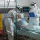 Medical nurse dressed in ppe suit putting oxygen mask to senior patient - PhotoDune Item for Sale