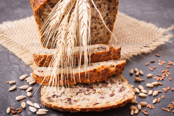 Loaf of wholegrain bread for breakfast, ingredients for baking and ears of rye or wheat grain - Stock Photo - Images