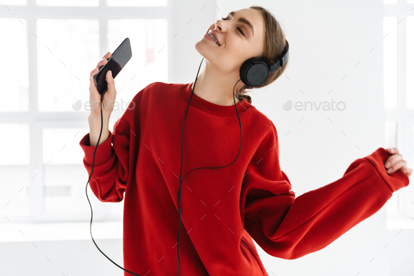 Happy woman dancing while listening music with headphones and smartphone - Stock Photo - Images