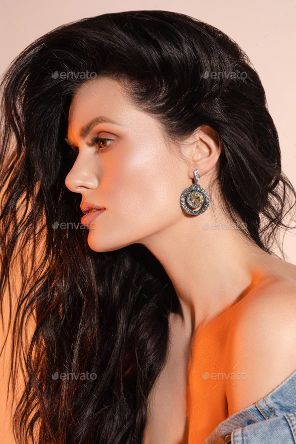 Pretty young woman with wavy hairstyle in studio - Stock Photo - Images