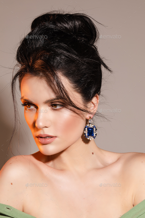 Beautiful young lady is demonstrating designer jewelry - Stock Photo - Images