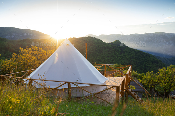 glamping tent in the morning sunlight with mountain range panorama - Stock Photo - Images