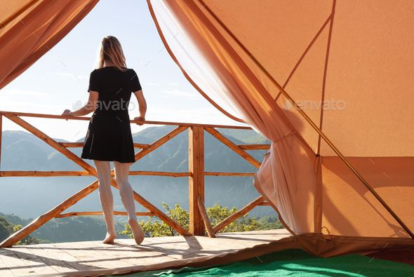 young woman watching the mountains in front of a glamping tent - Stock Photo - Images
