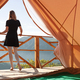 young woman watching the mountains in front of a glamping tent - PhotoDune Item for Sale