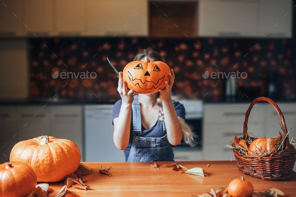Frightful Treats on the way. Portrait of housewife in the Halloween decorated kitchen holding a big - Stock Photo - Images