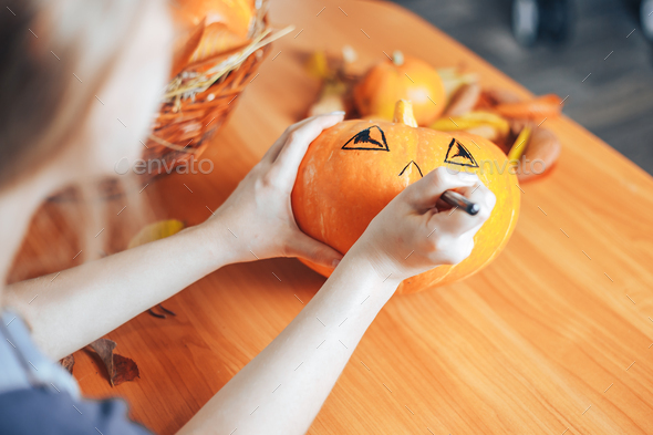 Preparation for Halloween: woman hands paint orange pumpkin with black paint. Closup. Holiday - Stock Photo - Images