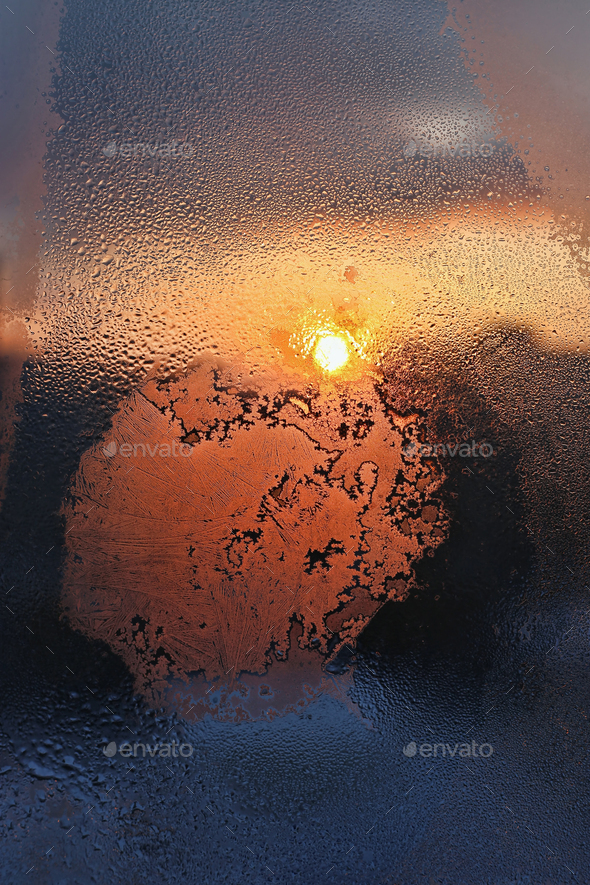 Ice patterns, water drops and sunlight on a winter window glasss - Stock Photo - Images