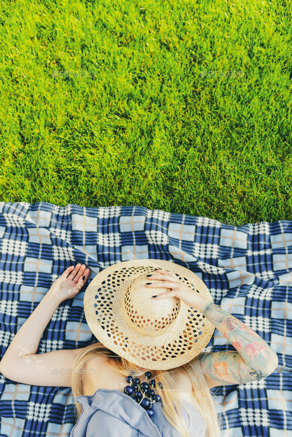 Mid Age Tattooed Woman Relaxing on Blanket in Backyard garden at Summer - Stock Photo - Images