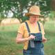 Female farmer using digital tablet in walnut orchard, innovative technology in organic farming - PhotoDune Item for Sale
