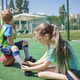 Older sister ties laces on boots to his brother during game on football field, fan support, sports - PhotoDune Item for Sale