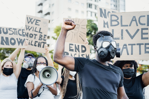 Activist wearing gas mask protesting against racism and fighting for equality - Stock Photo - Images