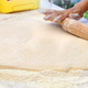 Woman chef rolls out yeast dough with a rolling pin on the table. - PhotoDune Item for Sale