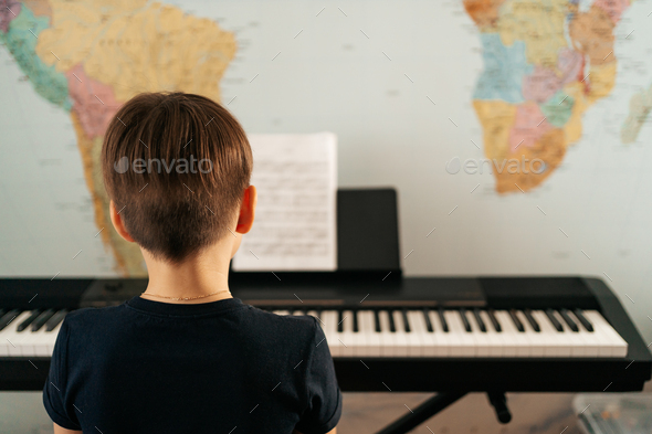 School boy playing synthesizer at home - Stock Photo - Images