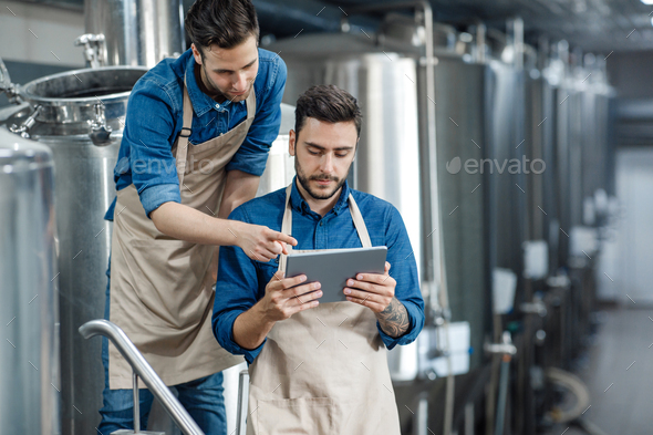 Men inspectors with digital tablet technician inspecting modern beer factory plant - Stock Photo - Images