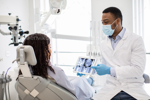 Male Black Dentist Doctor Demonstrating Female Patient Teeth Xray On Digital Tablet - Stock Photo - Images