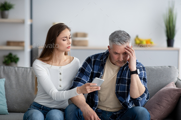 Mature woman confronting her husband about correspondence with his lover on smartphone - Stock Photo - Images