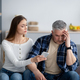 Mature woman confronting her husband about correspondence with his lover on smartphone - PhotoDune Item for Sale