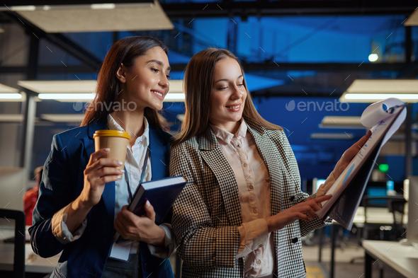 Cheerful women talks in night office - Stock Photo - Images