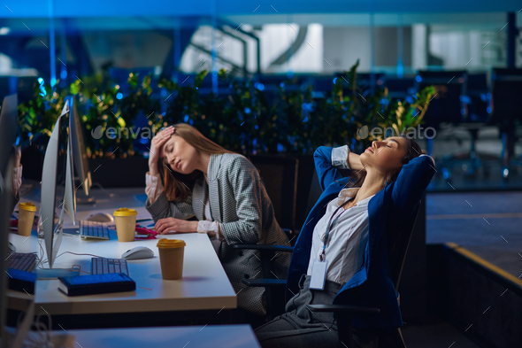 Tired women works on computers in night office - Stock Photo - Images