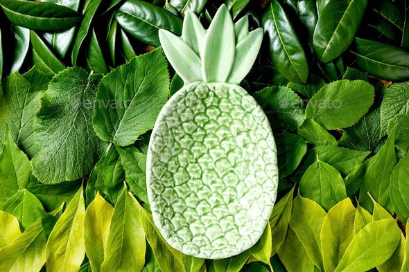 Ceramic green pineapple on background made of green leaves - Stock Photo - Images