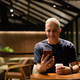 Portrait of man inside coffee shop at night using mobile phone - PhotoDune Item for Sale