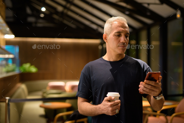 Portrait of man inside coffee shop at night using mobile phone - Stock Photo - Images