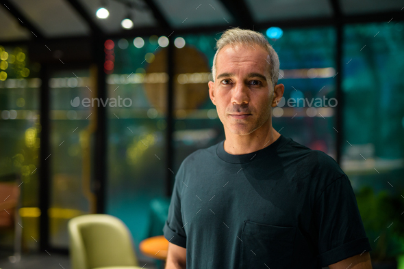 Portrait of man inside coffee shop at night looking at camera - Stock Photo - Images