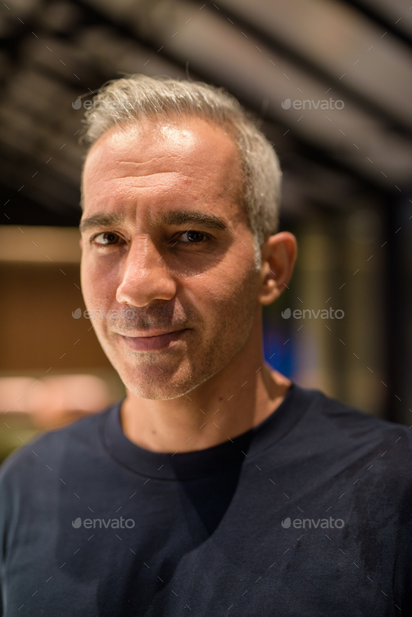 Portrait of man inside coffee shop at night - Stock Photo - Images