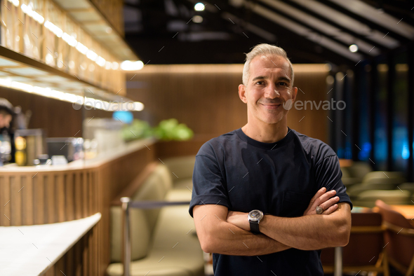 Portrait of man inside coffee shop at night smiling with arms crossed - Stock Photo - Images