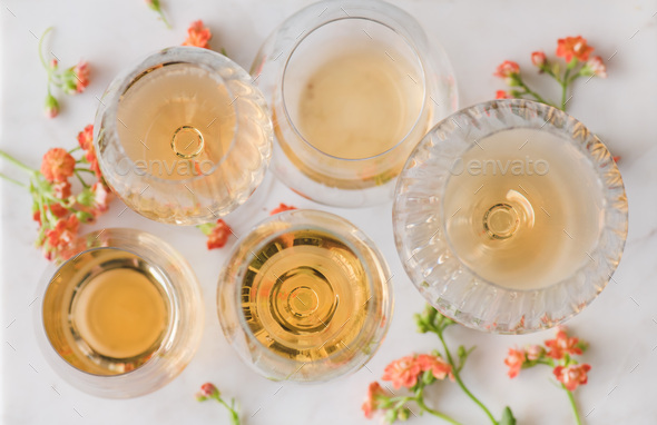 Orange or Amber wine and yellow flowers over white table - Stock Photo - Images
