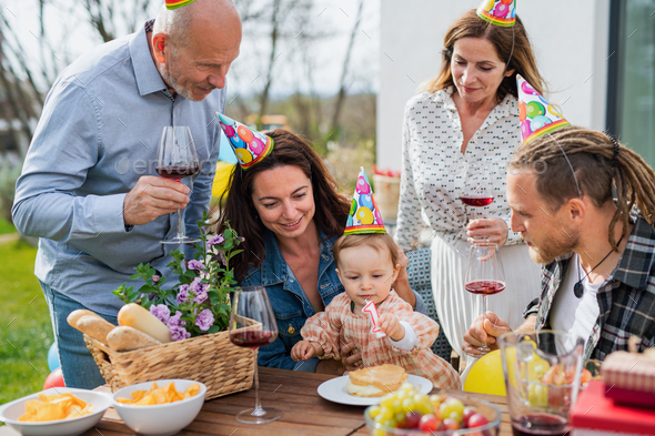 Happy multigeneration family outdoors in garden at home, birthday celebration party - Stock Photo - Images
