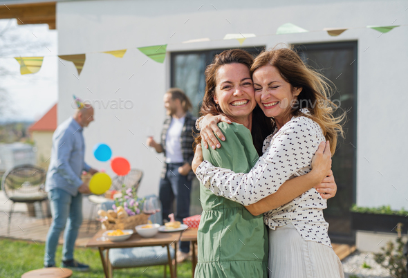 Young woman with mother outdoors in garden at home, birthday celebration party - Stock Photo - Images