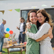 Young woman with mother outdoors in garden at home, birthday celebration party - PhotoDune Item for Sale