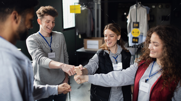 Group of volunteers at work in community charity donation center, fist bump - Stock Photo - Images