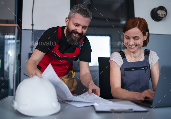 Man and woman workers or industry engineers with laptop indoors in factory, discussing issues - Stock Photo - Images