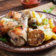 Baked chicken legs with slice potatoes and herbs. Barbecue chicken drumsticks on wooden table. - PhotoDune Item for Sale