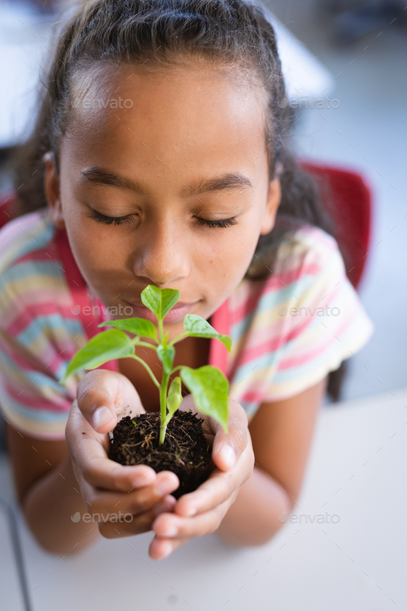 Close up of african american girl with eyes closed holding a plant seedling in the class at school - Stock Photo - Images