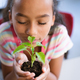 Close up of african american girl with eyes closed holding a plant seedling in the class at school - PhotoDune Item for Sale