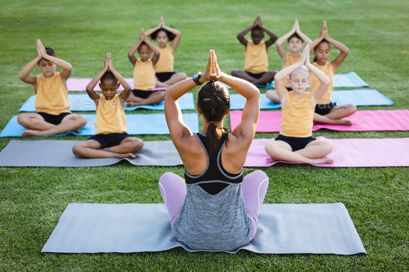 Female teacher and group of diverse students practicing yoga and meditating in the garden at school - Stock Photo - Images