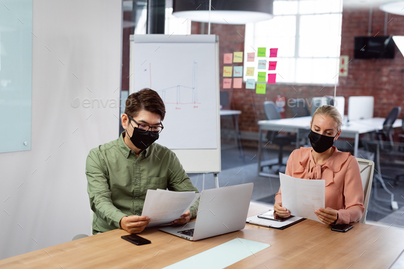 Diverse male and female colleague in face masks sitting at table with laptop reading paperwork - Stock Photo - Images