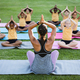 Female teacher and group of diverse students practicing yoga and meditating in the garden at school - PhotoDune Item for Sale