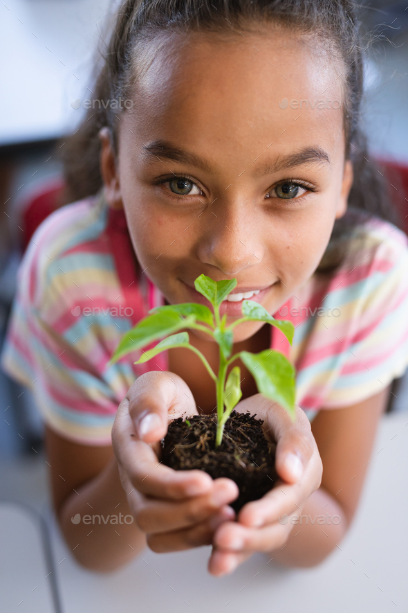 Portrait of african american girl holding a plant seedling in the class at school - Stock Photo - Images