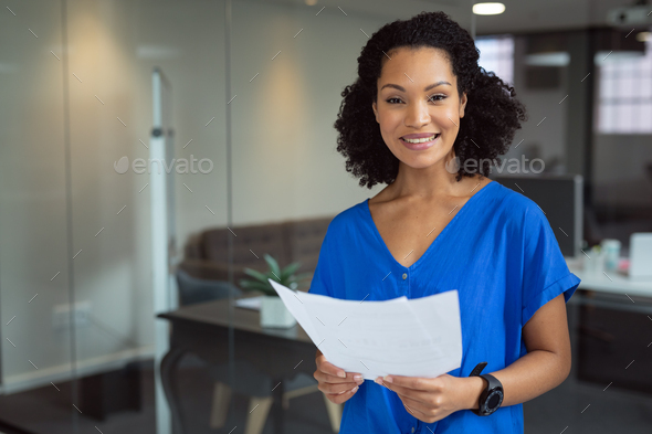 Portrait of smiling african american businesswoman holding paperwork standing in office - Stock Photo - Images