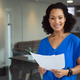 Portrait of smiling african american businesswoman holding paperwork standing in office - PhotoDune Item for Sale